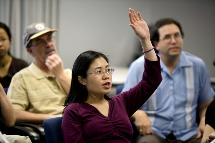 raising-her-hand-in-order-to-pose-a-question-this-asian-american-woman-725x483